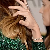 Olivia Wilde put her cocktail ring on display while fixing her hair.