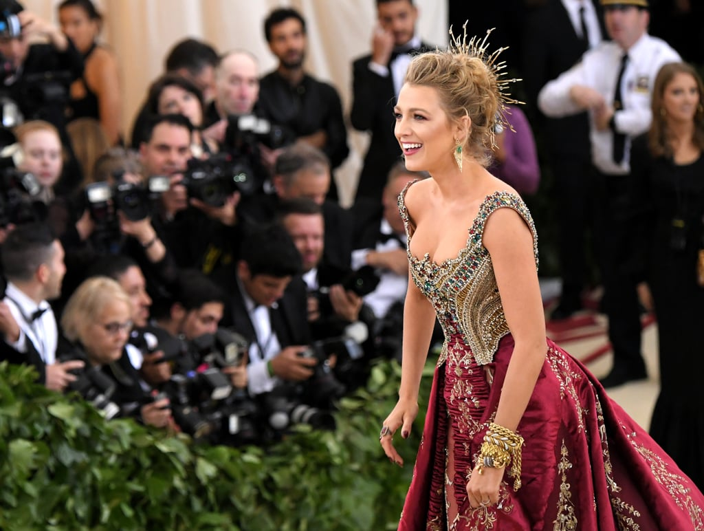 "Blake Lively was a vision in tk at the Met Gala in NYC on Monday night. The actress and mom of two walked the red carpet in an elaborate maroon and gold jewel-encrusted gown that stuck to the night's theme of ""Heavenly Bodies: Fashion and the Catholic Imagination."" Blake previously revealed that the creation took ""over 600 hours"" to make — well, the attention to detail paid off, because she looked amazing! Instead of bringing husband Ryan Reynolds as her date, Blake was joined by footwear designer Christian Louboutin. While Blake was serving looks at the Met Gala, Ryan is actually overseas promoting Deadpool 2 before its May 18 release; over the weekend, he and costar Josh Brolin performed on Rome's version of Dancing With the Stars.  Blake has been doing her own promotion, albeit a little more under-the-radar; last week, she wiped out her Instagram feed, unfollowed Ryan, played a creepy game of Hangman, and followed 23 people named Emily Nelson. The move was a way to call attention to her upcoming film A Simple Favor. Now that Blake is back on Instagram (and the red carpet) keep reading to see her fun night at the Met Gala."