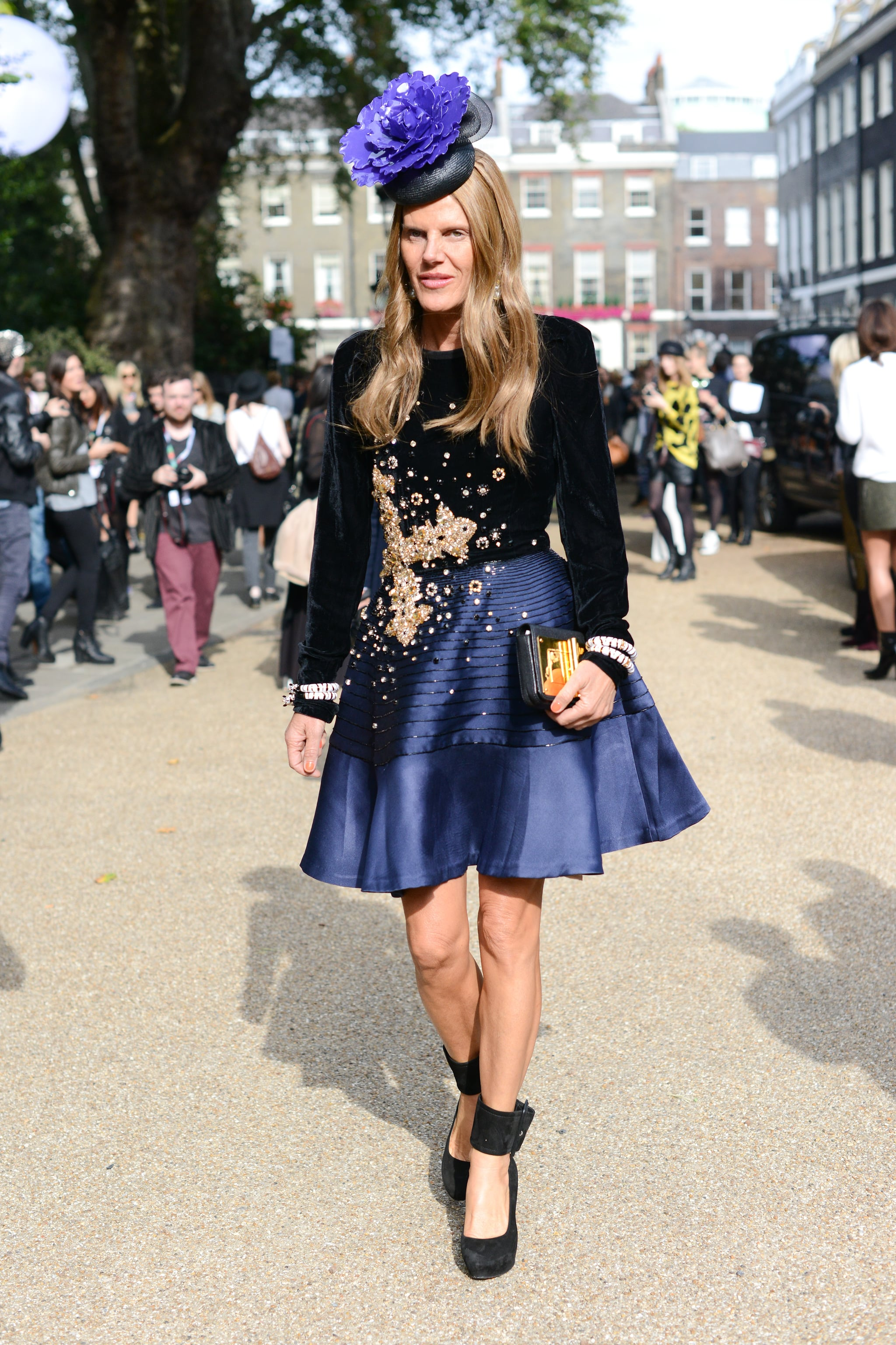 Anna Dello Russo stepped out in full regalia — with thick ankle-strap pumps and a purple fascinator completing her dramatic look.