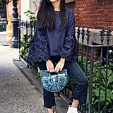 On Nikita: Sea NY shirt, Cult Gaia bag, Blank NYC jeans, and Neous boots.