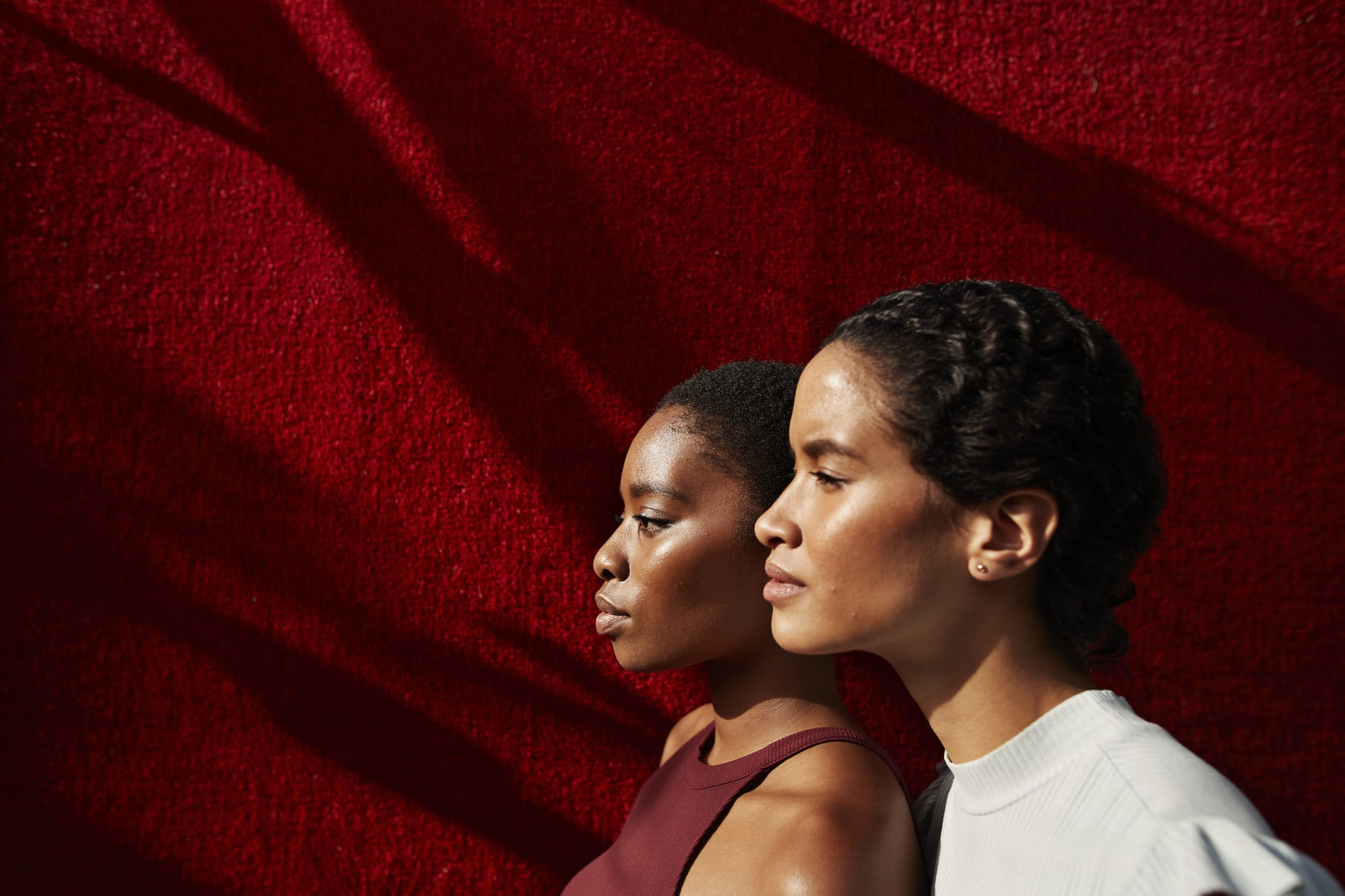 Side view of beautiful women standing against red wall