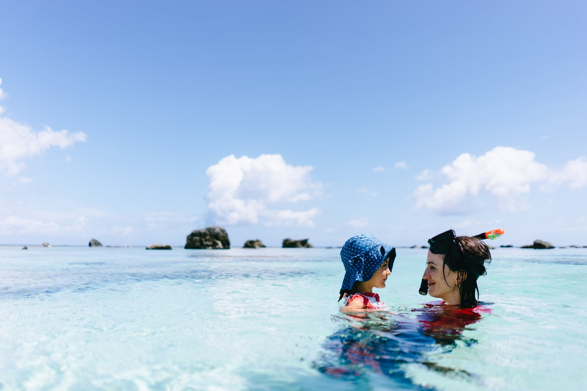 Mother and 3 year old toddler girl having intimate moment in clear tropical water, Amami Gunto National Park, Kagoshima, Japan