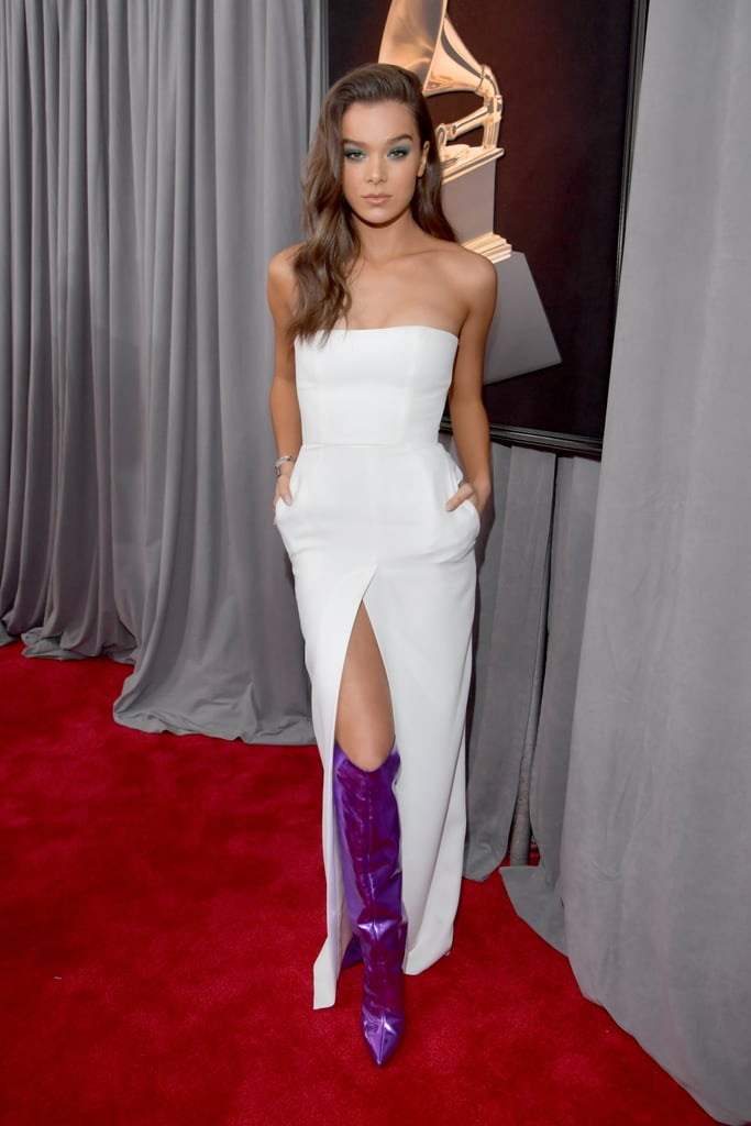 Hailee Steinfeld arrived at the 2018 Grammy Awards in a look that put all the focus on her footwear. The 21-year-old singer and actress wore a minimalist, strapless dress with a thigh-high slit by Alexandre Vauthier. While her dress was surprisingly simple, Hailee accessorized it with an eye-catching pair of knee-high, purple and metallic boots by the same designer. She opted to go without a handbag and completed her look with dazzling diamonds from Hearts On Fire, Djula, and Mattia Cielo. This is Hailee's first Grammy Awards appearance and she is set to present during the big show. See her futuristic look from all angles ahead.