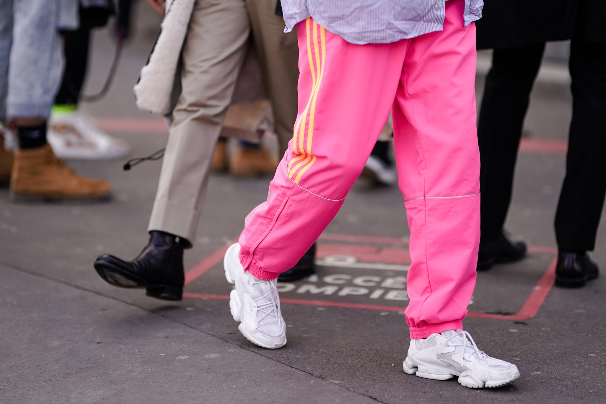 PARIS, FRANCE - JANUARY 18: A guest wears pink sports pants with yellow stripes, white sneakers, during Paris Fashion Week - Menswear F/W 2019-2020, on January 18, 2019 in Paris, France. (Photo by Edward Berthelot/Getty Images)