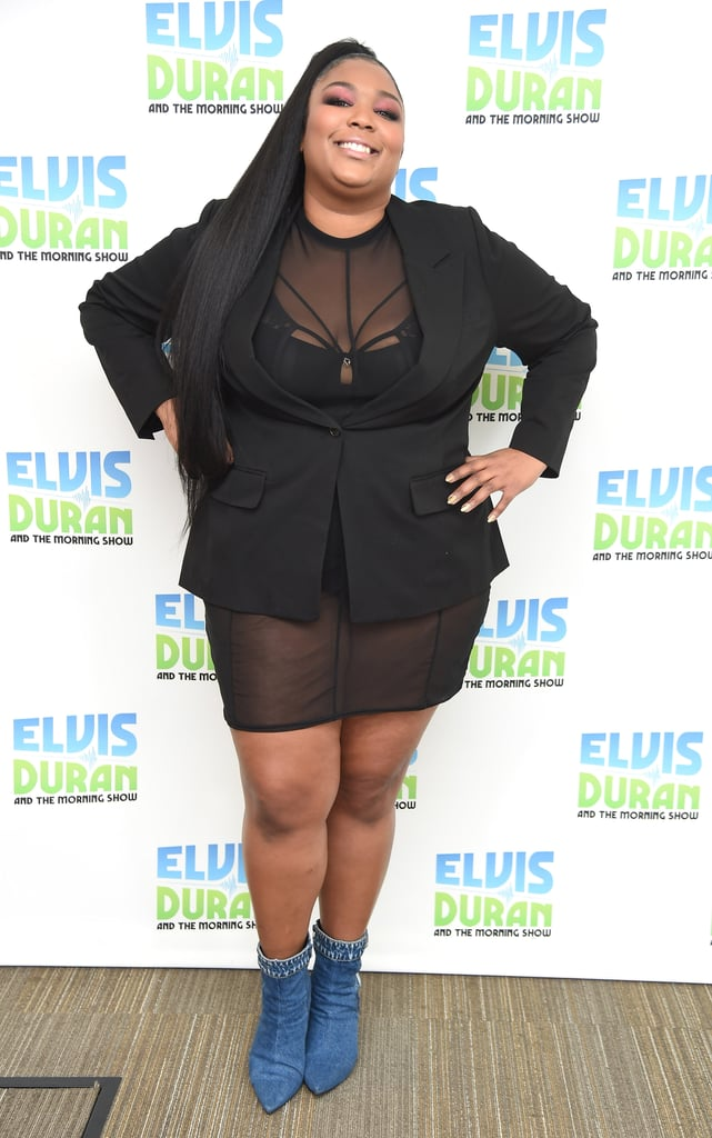 Lizzo visiting The Elvis Duran Z100 Morning Show in a sheer mini dress and a black blazer, paired with denim boots that make the entire outfit worth a double take.
