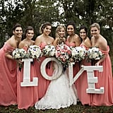 "Holding a sign that read ""LOVE,"" these bridesmaids wore the same shade of off-the-shoulder dresses."