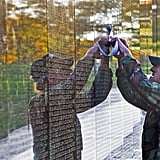 A veteran traced the name of a fallen soldier at the Vietnam Veterans Memorial wall in Washington DC.
