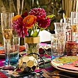 """The rich table setting is primed for lots of merriment and drinking. Justina explained, """"I gave each person three glasses! It just automatically makes everything feel fancy and special!"""" The rose-coloured wine glasses were hand-me-downs from Justina's grandmother. """"They have celebrated so many occasions with me and my family."""""""