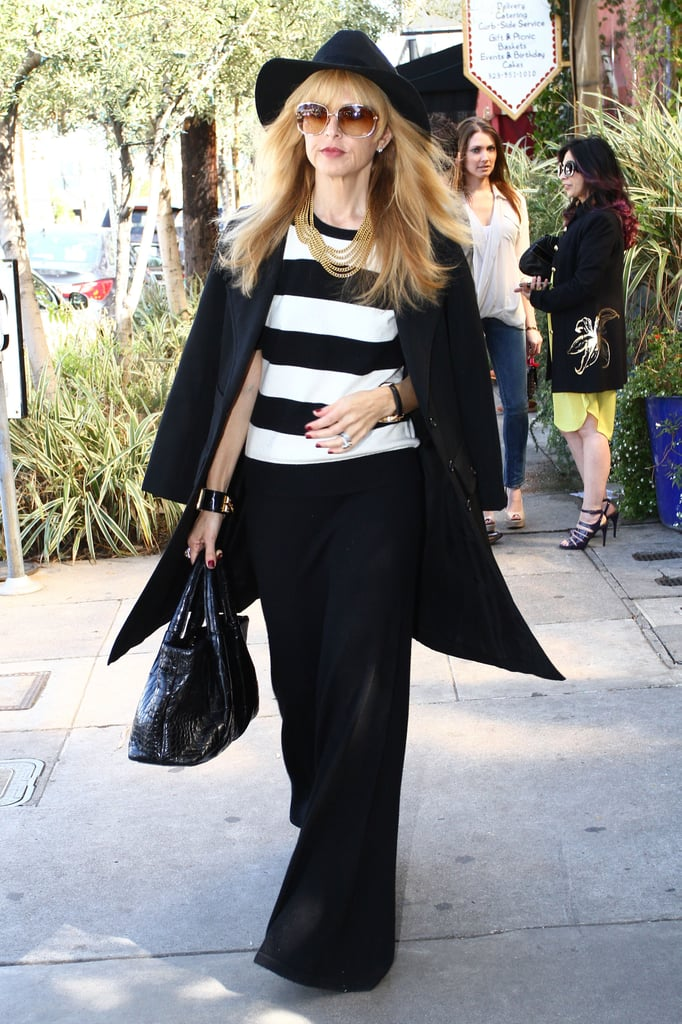 Rachel Zoe punched up her all black basics, wide-legged trousers, long coat, and panama hat with a striped black and white sweater while lunching in LA.