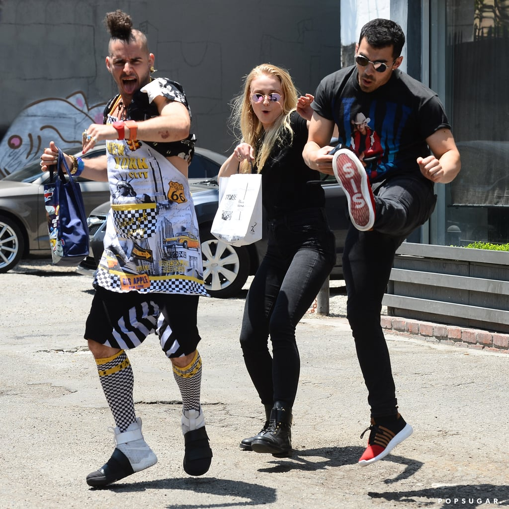 """Joe Jonas and Sophie Turner make one adorably goofy match. The couple, who first sparked dating rumors last November, put their sweet bond on full display during their recent day date in LA on Monday. Accompanied by Joe's DNCE band member Cole Whittle, the pair had a little fun with the cameras as they showed off their best karate moves. While the bassist donned his traditional loud prints, Joe and Sophie matched in dark-wash jeans, black tees, and circular sunglasses. The couple have had no problem showing PDA in front of the cameras recently. Aside from cuddling up on the beach in Mexico, Sophie revealed a very important fact about her beau by writing """"Joe gives me da good good"""" on her hand. Yep, we definitely can't get enough of their wacky love."""