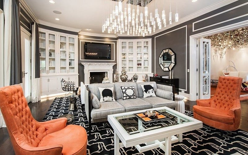 The orange theme continues in the adjacent room where a large-scale light fixture illuminates mod details, such as Jonathan Adler throw pillows and a geometric rug.