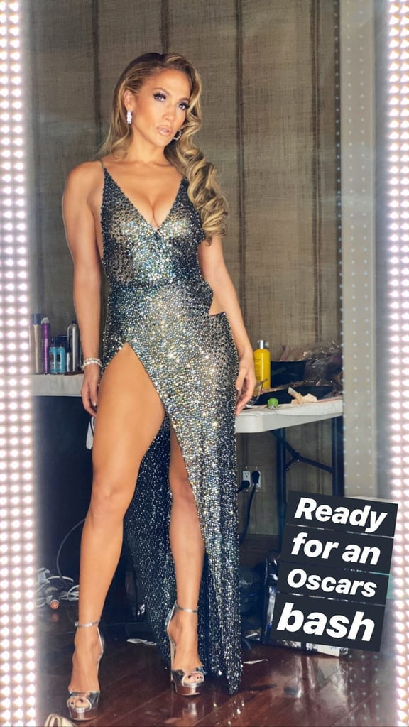Jennifer Lopez practically snuck into the Vanity Fair Oscars afterparty on Sunday night, but that didn't stop fans from admiring her gorgeous Julien Macdonald gown. After the celebrations died down, the Hustlers actress shared snaps of the dress she chose on Instagram, with the help of stylists Rob Zangardi and Mariel Haenn.  The liquid metallic dress from Macdonald's Spring/Summer 2020 collection featured delicate beaded detailing from top to bottom, with a subtle cutout at the hip. She topped off the emerald look with silver hoop earrings, heels, and a matching clutch, along with several sparkling jewelry pieces. Alex Rodriguez also looked dapper in his classic black tuxedo, and although they didn't pose together on the red carpet, the duo still made a stunning pair (as always) during their own photo shoot at home. Keep reading for a close look at Jennifer's gorgeous gown, from mirror pics to selfies and everything in between.