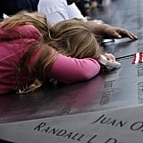 A young girl lays her head down on the 9/11 memorial during the ceremonies commemorating the 10th anniversary of the tragic attacks on the World Trade Center.