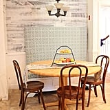 A boring kitchen corner is transformed into a charming, diner-inspired space with the addition of white-and-gray planks above the wainscoting.