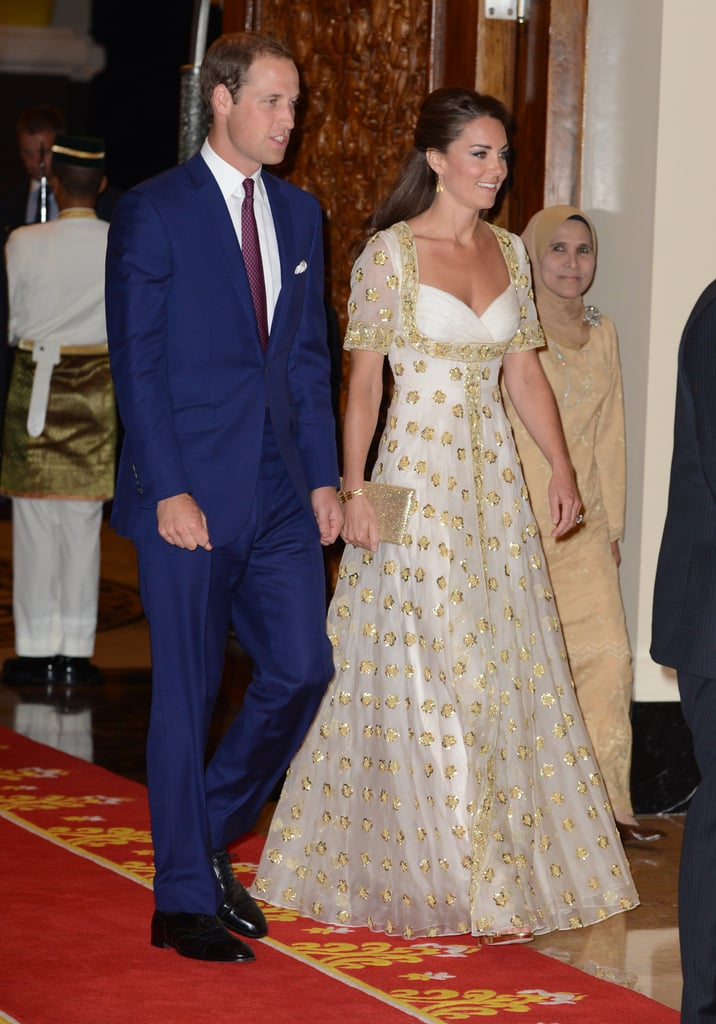 "Kate Middleton wore an embroidered white and gold Alexander McQueen gown this evening in Kuala Lumpur. The floor-length dress was covered with the national Malaysian flower, the hibiscus, in gold. She and her husband, Prince William, traveled to Malaysia earlier today for the second stop on their tour of the Asia Pacific region on behalf of Queen Elizabeth's Diamond Jubilee. This afternoon, Kate and William visited Hospis Malaysia as well. There, Kate gave her first speech abroad.  This evening, Kate and Prince William changed into their formalwear for a dinner hosted by Malaysia's head of state, Sultan Abdul Halim Mu'adzam Shah of Kedah. The meal took place at the Istana Negara, the national palace and official residence of the King of Malaysia. Kate reflected on her speech, and expressed relief that it was over. She said, ""I was so nervous and I am very glad that it is over with. There was an amazing atmosphere."" Prince William, meanwhile, spoke about their upcoming travel to the island of Tuvalu. He said, ""We hope to do some fishing and snorkeling. I am very interested in the coral and whale sharks. I have dived with them before and although they are huge, they are very docile creatures — not like jaws!"""