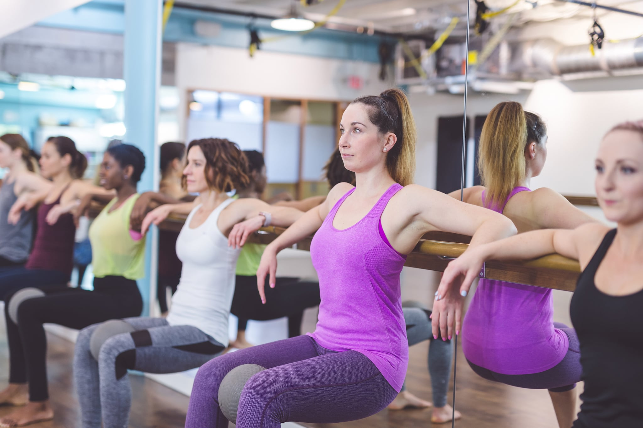 Multiethnic group of young women do barre & TRX suspension workout together at modern gym suspension workout together at modern gym