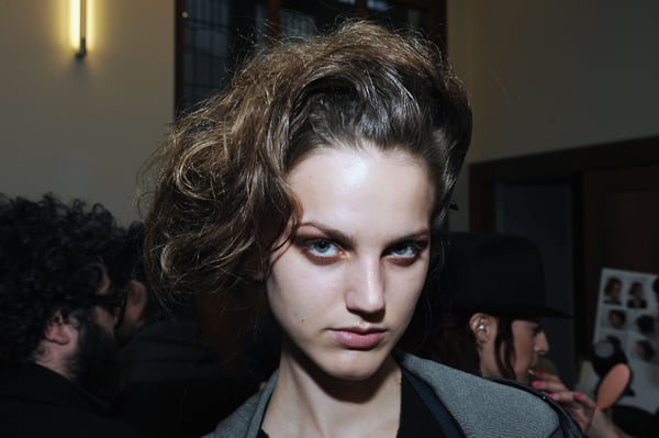 """It's a Hollywood-meets-New York inspiration,"" lead stylist Odile Gilbert said of the show's textured hair. In front, a glamorous swoop; in back, twists and braids. Gilbert created the complex look by adding Kérastase Mousse Volumactive to dry hair, then scrunching with hands. A little Lotion Densitive, also by Kérastase, added volume and texture."