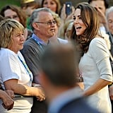 Kate laughs with a couple.