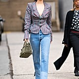 Wearing a striped blazer by Vivienne Westwood with Re/Done jeans and a suede Birkin bag.