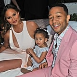 Chrissy and John, sitting with Luna, flash a couple of smiles at the camera at John Legend's launch of his new rose wine brand, LVE, during an Airbnb Concert in June 2018.
