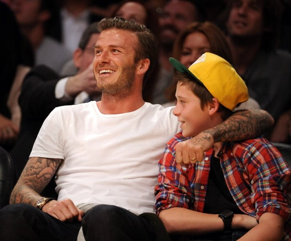 David and Brooklyn Beckham had floor seats for the Lakers game in LA yesterday. The boys snacked on nachos and chatted with Denzel Washington during the matchup, which ended with the home team beating the Miami Heat. It was an extra special outing for Brooklyn, since it was his 13th birthday. The fun continued with a bash at the Beckhams' house, where their dog Coco got into the celebration by wearing a party hat and Victoria shared a snap of the pup's festive look on Twitter. David and Victoria are coming off a busy few weeks that included a stop in NYC for Fashion Week and an appearance at Vanity Fair's Oscar party.