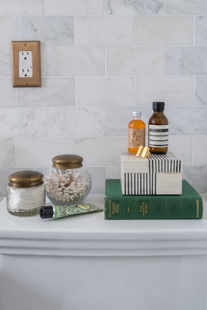 Why not take advantage of the space above the toilet? Sandie styled it with jars filled with Q-tips and cotton pads, bath products, a reading book, and a chic trinket box. Photo by Samantha Goh via Homepolish