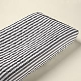 Even the less glamorous essentials can be striped, like this striped changer pad cover ($35) in a fresh gray shade.