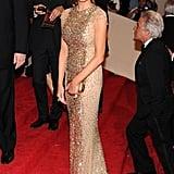 Melania attended the Alexander McQueen: Savage Beauty Met Gala in 2011 wearing a gold Reem Acra dress.