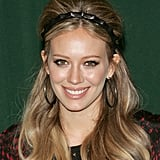 Serious backcombing is required to get Hilary Duff's look, but leave a small section free at the front. Part this in the centre, and use a headband to secure the two strands at the ears. Then pull these strands, plus the top half of the backcombed hair into a ponytail at the nape of the neck, leaving the rest of the hair loose over the shoulders.