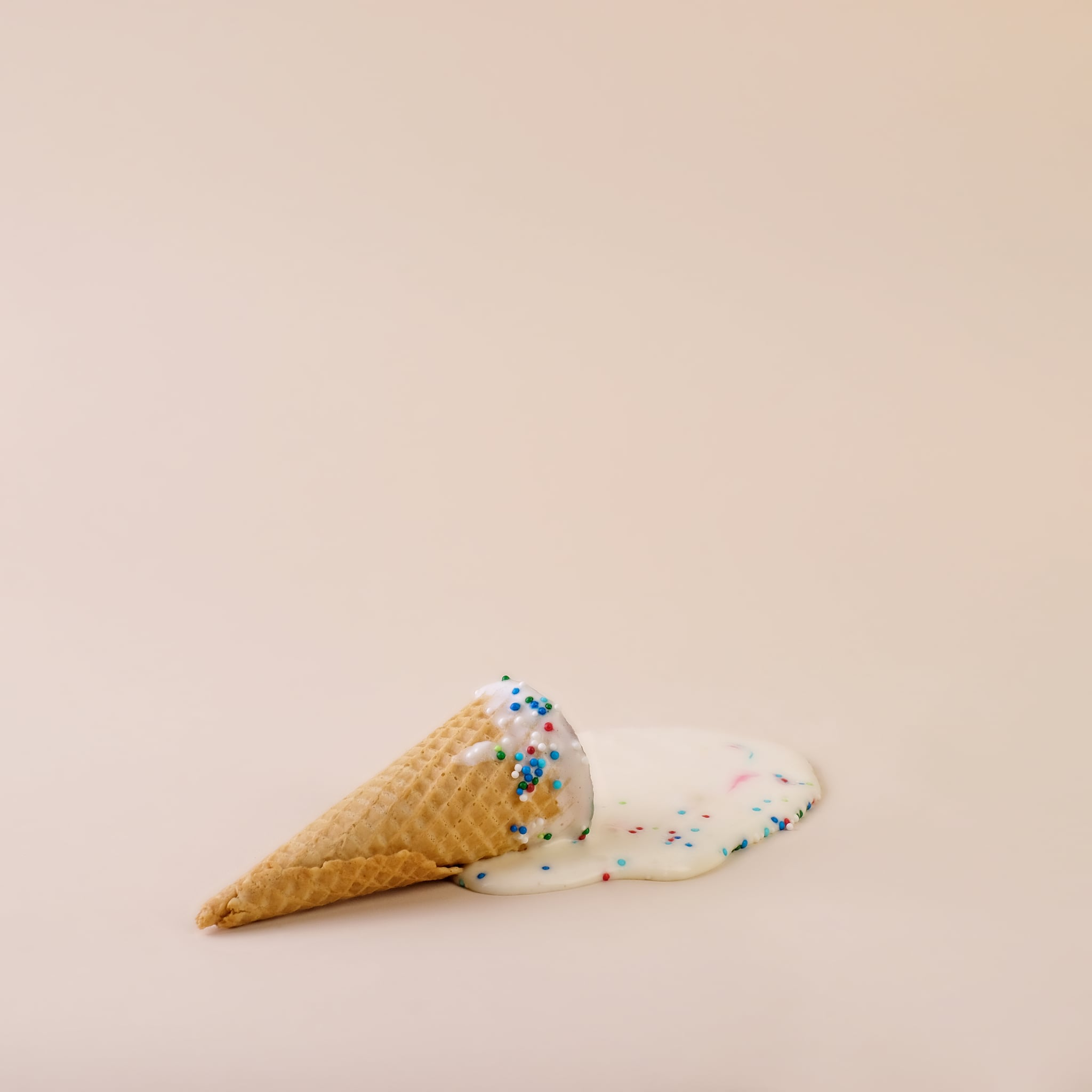 Puddle of melted ice cream with cone and sprinkles.