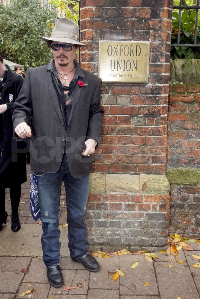 """Johnny Depp was in a hat, sunglasses, and plenty of necklaces yesterday to pose outside the Oxford Union in England. The private debate club was one of many stops on Johnny's UK press tour for The Rum Diary, and members were eager to hear what the actor had to say. Organizers raffled off tickets to hear Johnny speak after demand far exceeded the 500-seat capacity of the theater! Johnny also spoke to the London paper The Guardian about his new movie, friendship with author Hunter S. Thompson, and love for Europe. Johnny admitted to really not disliking anything about European ways of life. He said, """"It's a very old and beautiful culture, people know how to live. You know, [in London] you have Sunday roast or the pub lunch, that kind of thing. It's comforting. We don't have that in our culture in the States. Sunday is football day, so it's chicken wings and pizza."""""""