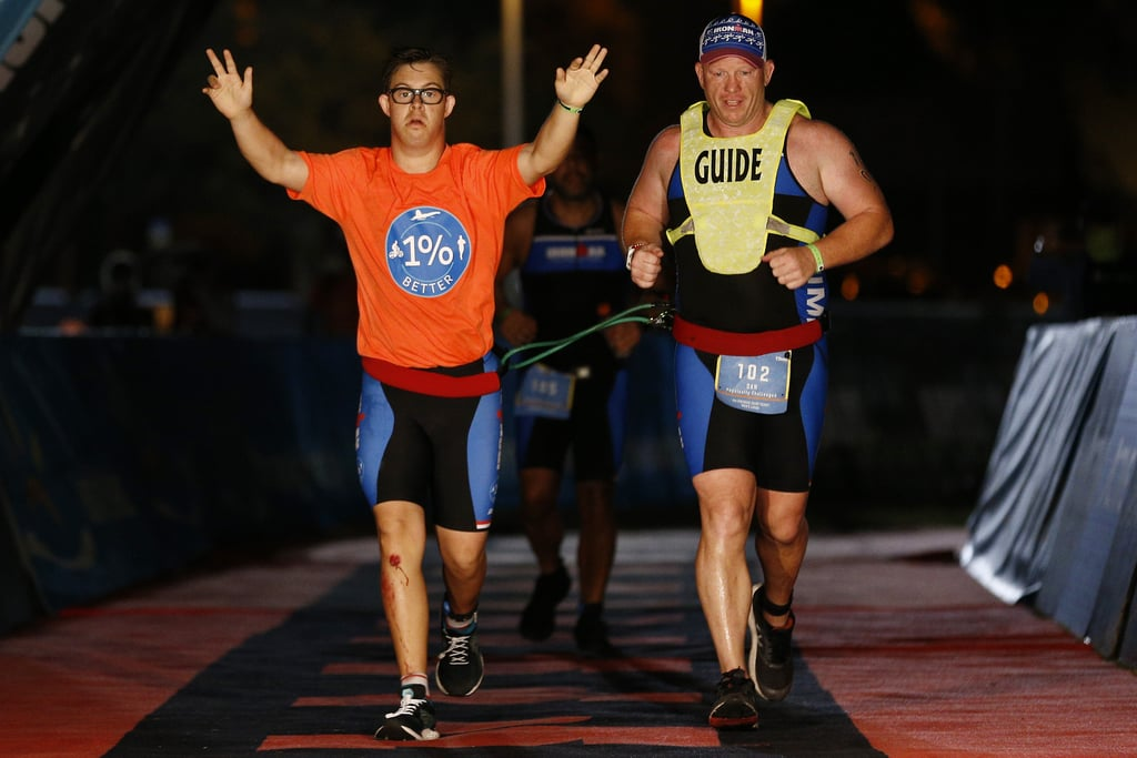 """On Nov. 7, 21-year-old Chris Nikic became the first person with Down syndrome to attempt and finish an Ironman, swimming 2.4 miles, biking 112 miles, and completing a full marathon in 16 hours, 46 minutes, and nine seconds. Nikic, a Special Olympics Florida athlete, was alongside guide and coach Dan Grieb, who has raced in 16 Ironmans, according to Today.com. Over the past year, Nikic, from Maitland, FL, trained with Grieb, and the initial goal was a half Ironman. When that race was postponed in May due to the COVID-19 pandemic, he set his sights on the full Panama City Beach Ironman taking place on the weekend following Election Day in the US. During the race on Nov. 7, Nikic was tethered to Grieb for the swimming and running portions. """"From the time he was born, we were told by everyone that he'd never do anything or amount to anything or be able to accomplish anything [beyond] being able to tie his own shoes,"""" Nikic's father told Orlando Sentinel. """"And we believed them for the longest time."""" Nikic underwent open heart surgery at just 5 months old and couldn't walk until he was 4. However, with his training, Nikic said to Sports Illustrated En Fuego, """"I learned that I am willing to work hard and get one percent better every day."""" He added, """"But I also learned that I can get my dream."""" Next up, he hopes to make history again at the Ironman World Championship in Kona, HI, in October 2021. """"The opportunities you have created for others around the world through this journey you embarked upon, is immeasurable,"""" Ironman wrote on its Instagram page. """"Thank you for allowing us to be a part of your remarkable life story and we can't wait to see what you achieve next."""" Check out pictures from Nikic's history-making Ironman race ahead.      Related:                                                                                                           YouTuber Molly Burke Became Depressed After Losing Her Eyesight — Here's How She Coped"""