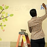 The First Lady paints iconic MLK quotes onto a library wall.