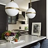 "To create the modern, bright kitchen, Antonio opened up a wall and added a breakfast bar. The designer didn't stress about pairing brass hardware on the cabinet pulls and the Circa Lighting pendants with stainless finishes. ""Mixing metals is a much more relaxed approach,"" he told Elle Decor."