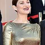 At the premiere of From the Land and the Moon, Marion Cotillard let her gleaming dress stand out, keeping her makeup pared down save for a crimson lip.