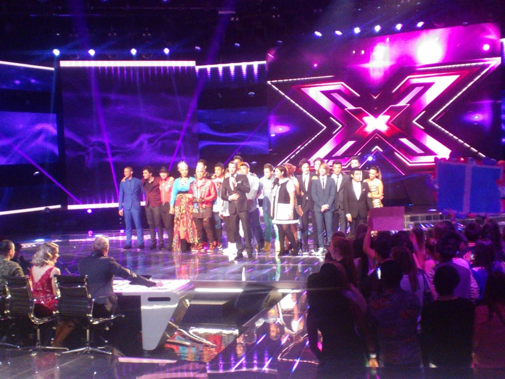 The top 11 acts from The X Factor come together at the end of the performance show. Want some insider info on what it's like to go to a recording? Firstly, it's long. You need to get to the studio two hours before the show starts so they can do pre-records and make sure everyone's in place. And there's a lot of waiting. There's also a warm-up guy to keep the audience entertained in commercial breaks and to also make sure things run smoothly, which means double-checking fan posters to make sure nothing naughty or rude makes it to air.
