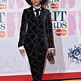 At the Brit Awards, Janelle dressed up a patterned velvet suit with a ruffled shirt, black necktie, and strappy lace sandals, not to mention a wide-brimmed black hat.