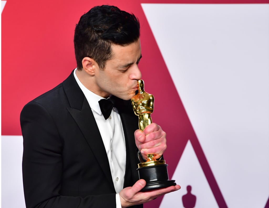 One might say Rami Malek is living his best life. During award season he swept the board, winning an Oscar, a SAG award, a BAFTA, a Golden Globe . . . the list goes on. But it's not just the wins that represent Rami's best. He's also had plenty of funny award season moments. May we remind you of his gloriously awkward moment with Nicole Kidman, or the adorably pure moment when he introduced himself to Lady Gaga?  It turns out, he was just getting started with cute tidbits. The Oscars was when the Bohemian Rhapsody actor really shone. He went full Champagne Rami while waiting for his award to be engraved, fell off the stage and had paramedics tend to him (he was OK), and kissed every Oscars attendee he could find. Ahead, see every single photo from Rami's big night. He should honestly win an extra award for being the most entertaining guest.