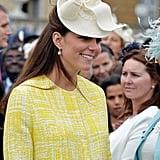 أتمّت كيت سترتها ذات اللّون الأصفر بقبّعة من تصميم جين كوربيت في حفل أُقيم بحديقة القصر عام 2013.