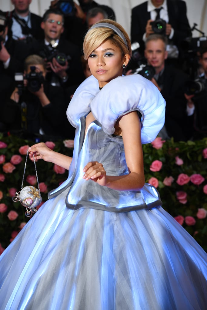 "Zendaya had a Cinderella moment at the 2019 Met Gala — because she was actually dressed like the Disney princess. Wearing a baby blue Tommy Hilfiger gown made to look nearly identical to the one in the nostalgic animated film, Zendaya waited at the end of the red carpet for her stylist, Law Roach, to wave a wand, which gradually lit up her gown from the bottom up! Because she's an actress, Zendaya also committed to the role by ""accidentally"" dropping her glass slipper on the steps of the Met. Don't you just hate it when that happens?      Related:                                                                                                           Katy Perry Wore a Chandelier on the Red Carpet, So Yeah, the Met Gala Is Lit"
