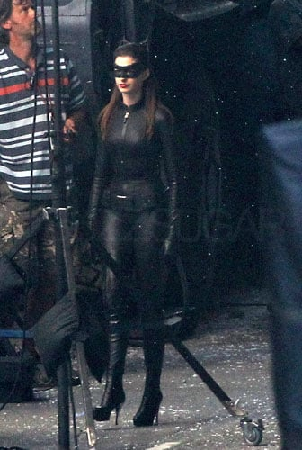 It's not every day you see Batman and Catwoman having a laugh together, but that's exactly what happened on the set of The Dark Knight Rises over the weekend. Christian Bale and Anne Hathaway gave us yet another peek at their costumes, but it's definitely the cat suit that's getting this most attention here. We've already seen Anne Hathaway riding the Bat pod, but now she's got a different set of eyewear and a sexy skintight suit. It looks more like Batman's suit than what we've seen from other big-screen versions of the character, but personally I'm glad that director Christopher Nolan left the shiny vinyl at home.