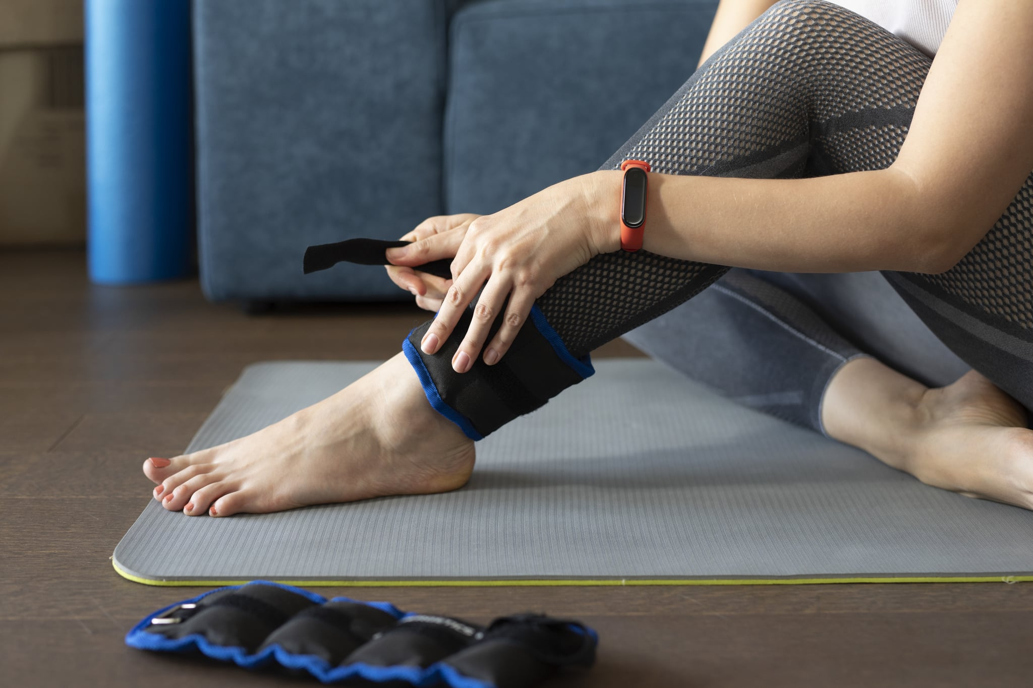 Anonymous woman putting ankle weights on her legs to work out at home.