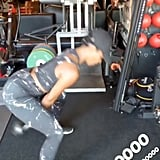 With her legs spread apart and both hands on the kettlebell, she swung the weight between her legs . . .