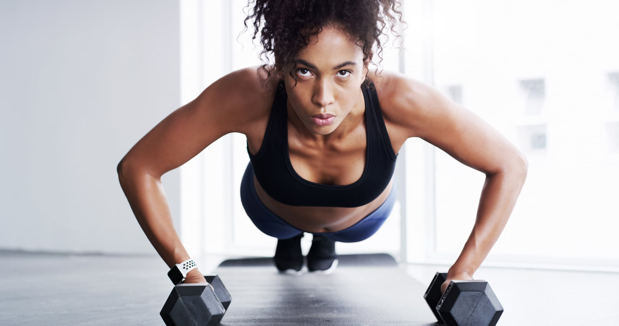 Shot of a young woman working out with dumbbells in a gym