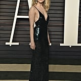 At the 2016 Vanity Fair Oscars party wearing an emerald sequinned dress from Calvin Klein Collection with Chopard jewelry and Roger Vivier shoes.