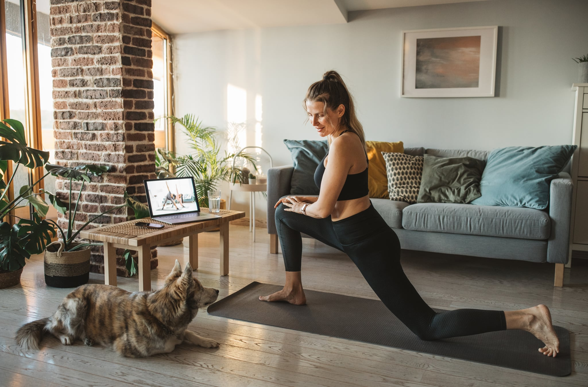 Women at home during pandemic isolation doing online yoga class
