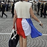 A woman dons a French flag dress and a cockade in her hair to attend the annual Bastille Day parade in Paris.