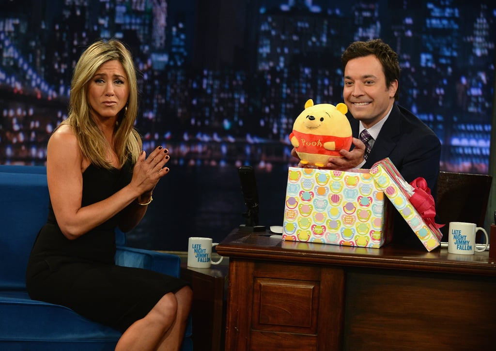 """Jennifer Aniston made a stop by Late Night last night ahead of her big premiere for We're the Millers in NYC. She showed love for Jimmy's new daughter, Winnie Rose, by giving the talk show host an adorably round Winnie the Pooh bear stuffed animal. The small gift came with some extra Aniston love, as she revealed that she actually slept with the toy the previous night because it's """"so cuddly."""" This being Late Night, Jennifer also got a chance to get in on some fun antics and took part in a celebrity Pictionary game with Jimmy, Lenny Kravitz — who played for Team Aniston — and CeeLo Green. Surprisingly, Jennifer is actually really good at playing Pictionary! Watch Jennifer Aniston play Pictionary, and keep clicking to see more snaps from her Late Night stop."""