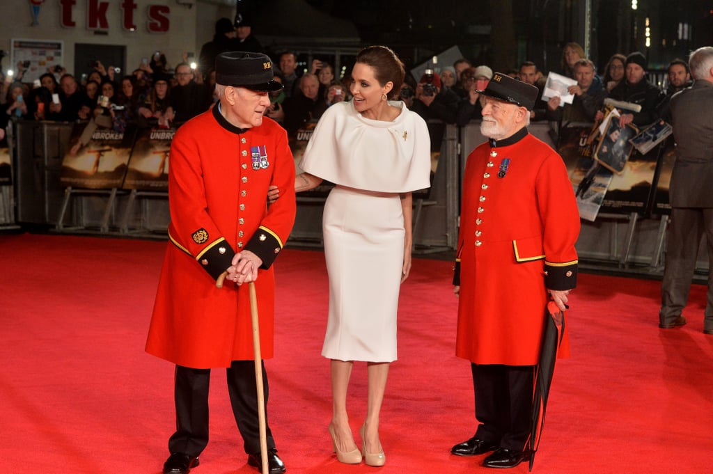"""Angelina Jolie was a vision in white when she attended the London premiere of her latest project, Unbroken, on Tuesday. While Brad Pitt was nowhere to be seen on the red carpet, the actress-turned-director instead split her time between her film's star, Jack O'Connell, and chatting up two Chelsea Pensioners who attended the event in their trademark scarlet uniforms. It's been a busy week for Angie, who recently opened up to Tom Brokaw about her new life as a married woman, saying that she wanted to learn how to cook in order to be """"a better wife"""" for Brad. (However, it sounds like Brad is just fine with her not picking up any culinary skills.) Angie and Jack have both been doing quite a bit of press as they prepare for the Christmas release of their new film. The two traveled to Sydney last week to premiere the project in Australia, and they both popped up at the 2014 Hollywood Film Awards in LA, where Jack scooped up the new Hollywood award."""
