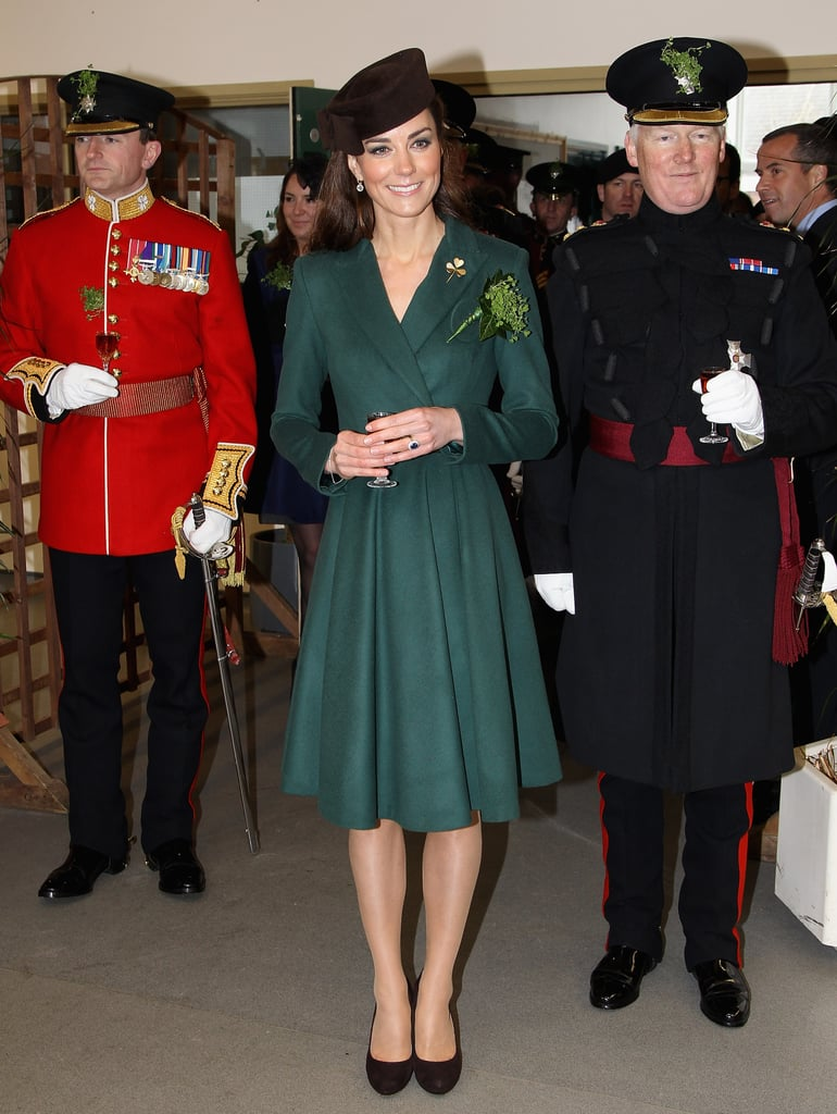 Kate Middleton belted her green Emilia Wickstead dress at a St. Patrick's Day event with Irish Guards in Aldershot, England today. She accessorized her emerald look with a gold clover brooch that belonged to the Queen Mother. Kate watched the traditional parade with a smile before handing three-leafed clovers to 40 lucky officers and one to their canine mascot, an Irish Wolfhound. When the presenting of shamrocks ceremony was complete, Kate went inside the barracks and sipped on sherry before attending a luncheon. It's been a busy week of appearances for the Duchess, who also showed off her hockey skills at the Olympic Park and visited the Prince's Foundation For Children and the Arts at the Dulwich Picture Gallery with Prince Charles.